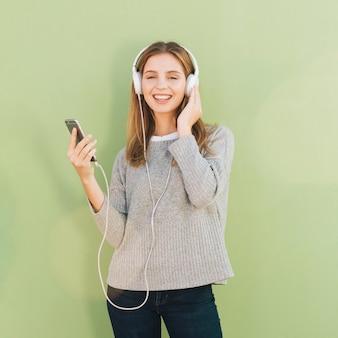 Música que escucha sonriente de la mujer joven en el auricular contra fondo del verde menta