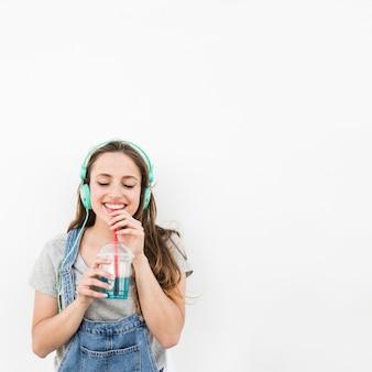 La música que escucha sonriente de la mujer joven en el auricular goza de beber el jugo sobre el contexto blanco