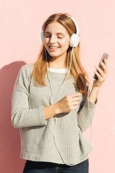 Música que escucha sonriente de la mujer joven en el auricular a través del teléfono móvil