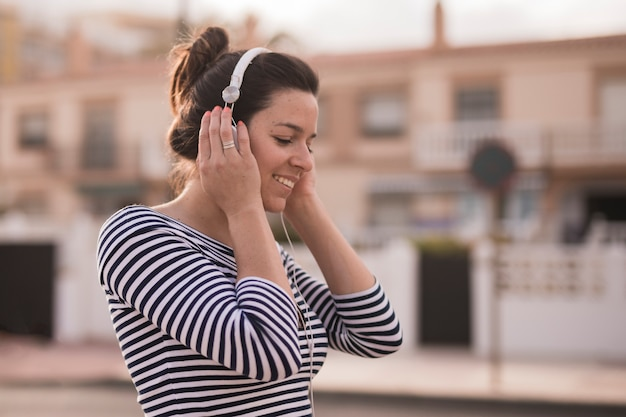 Música que escucha sonriente de la mujer joven en el auricular