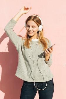 Música que escucha sonriente de la mujer joven en el baile del auricular contra la pared rosada