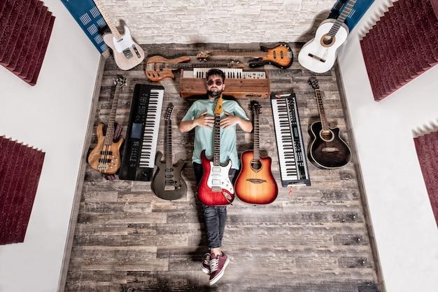 Músico acostado en el estudio de música con guitarras y pianos.
