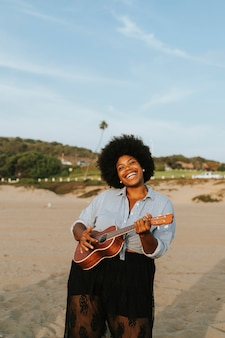 Músico afroamericano tocando el ukelele en la playa
