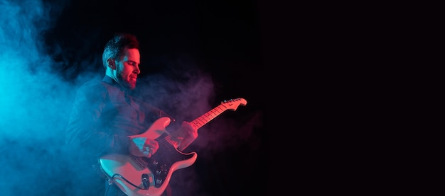 Músico aislado en estudio oscuro en luz de neón