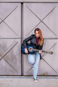 Músico de la calle tocando la guitarra acústica joven vistiendo chaqueta al aire libre