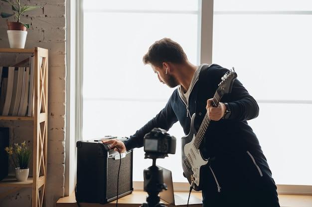 Músico caucásico tocando la guitarra durante un concierto en línea en casa aislada y en cuarentena, alegre improvisación