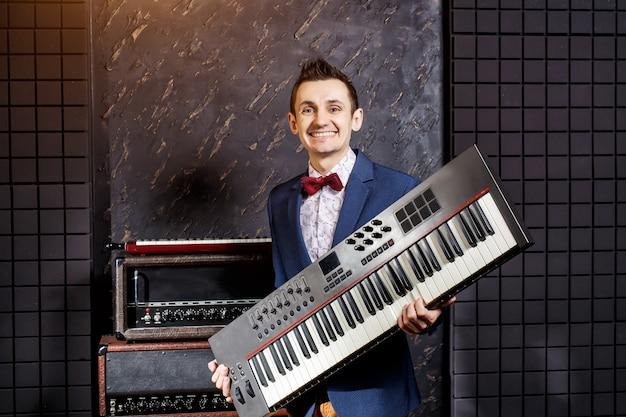 Músico con una chaqueta azul y una mariposa roja con un sintetizador en las manos en un estudio de grabación