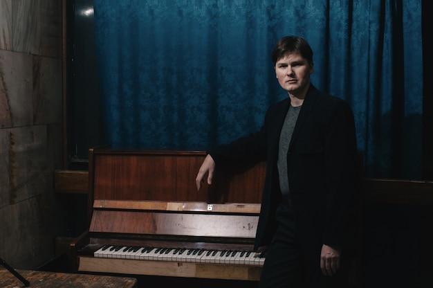 Músico clásico intérprete cerca de piano. artista musical en el cuarto oscuro de la casa de la cultura. retrato de hombre creativo en clave baja. compositor cerca de instrumento musical.