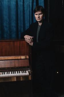 Músico clásico intérprete cerca de piano. artista musical en el cuarto oscuro de la casa de la cultura. retrato de hombre creativo en clave baja. compositor cerca de instrumento musical