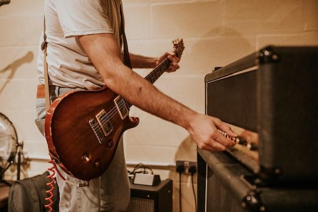 Músico configurando amplificador de guitarra, sesión de grabación de estudio foto