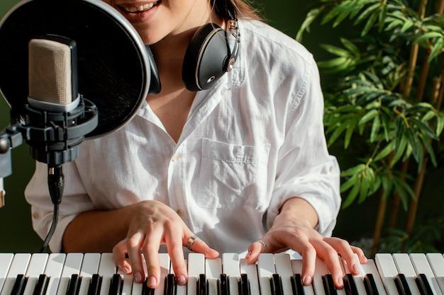 Músico femenino sonriente tocando el teclado del piano en el interior y cantando en el micrófono