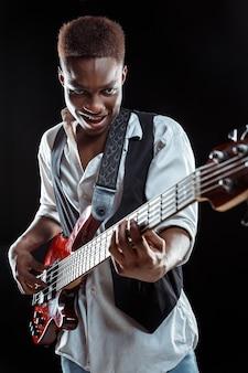 Músico de jazz guapo afroamericano tocando el bajo en el estudio sobre un fondo negro. concepto de música. chico atractivo alegre joven improvisando. retrato retro de primer plano.