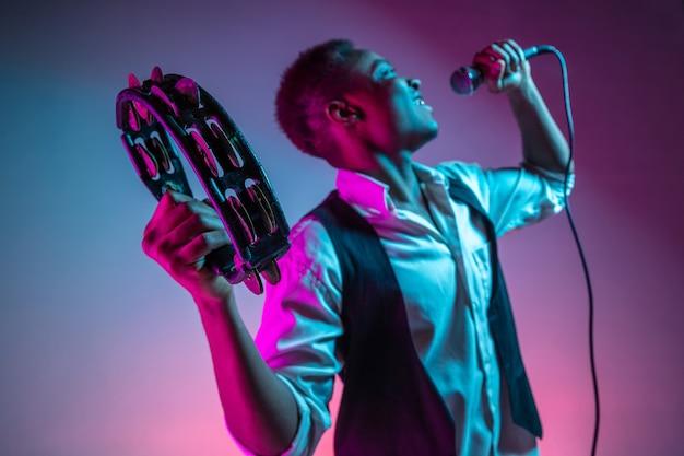 Músico de jazz guapo afroamericano tocando pandereta y cantando.