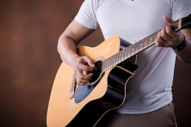 Músico joven asiático con guitarra acústica