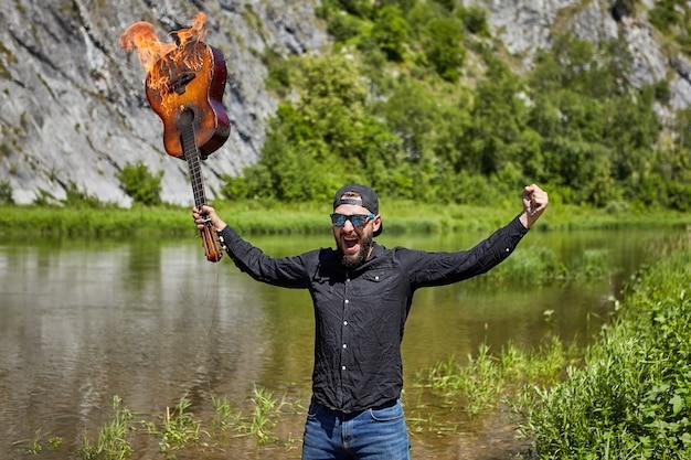 Músico loco levantó la guitarra en llamas con el telón de fondo del río salvaje.