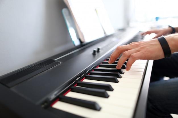 Músico masculino manos tocando el piano eléctrico moderno