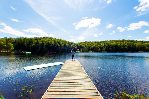 Músico de pie frente al lago bajo un cielo soleado