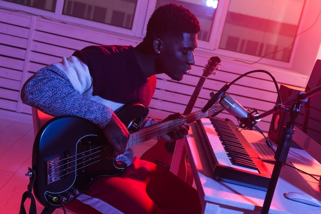 Músico profesional afroamericano grabando bajo en estudio digital en casa, música