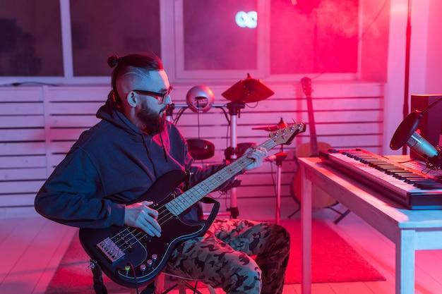 Músico profesional grabando bajo en estudio digital en casa, tecnología de producción musical