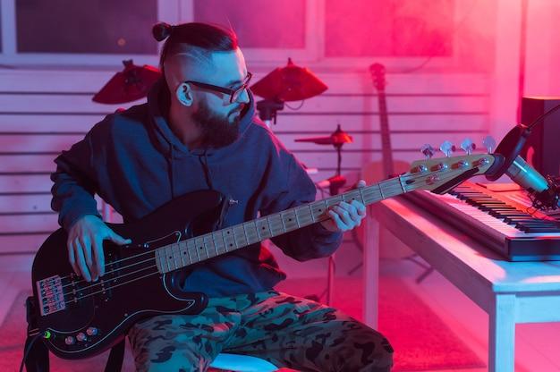 Músico profesional grabando guitarra en estudio digital en casa