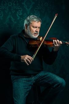 Músico senior tocando un violín con varita en negro