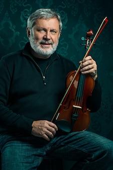 Músico senior tocando un violín con varita en pared negra