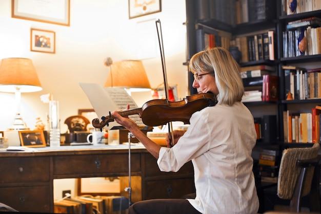 Músico senior tocando un violín