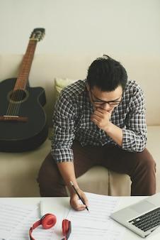 Músico sentado en el sofá y escribiendo una canción, y una computadora portátil, auriculares y guitarra tumbados