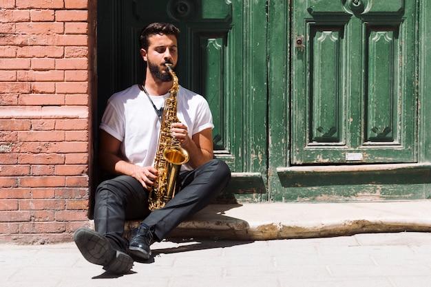 Músico sentado y tocando el saxofón.