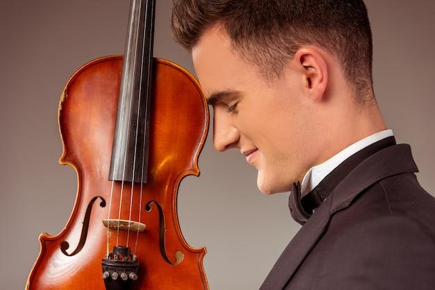 El músico de sexo masculino se coloca con un violín.