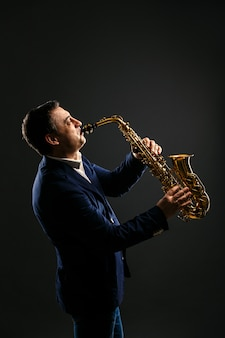 Músico toca jazz en el saxofón. oscuro