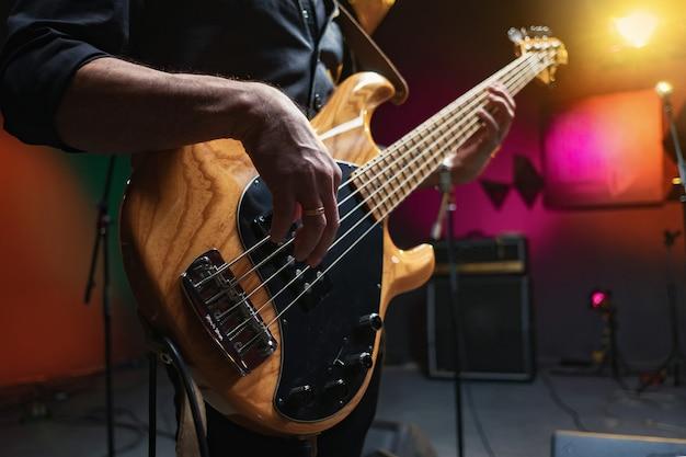 Músico toca bajo, primer plano, estudio de grabación