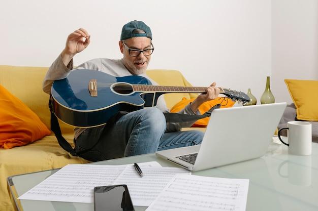 Músico tocando la guitarra y componiendo música con sus colegas por videoconferencia a través de su computadora portátil