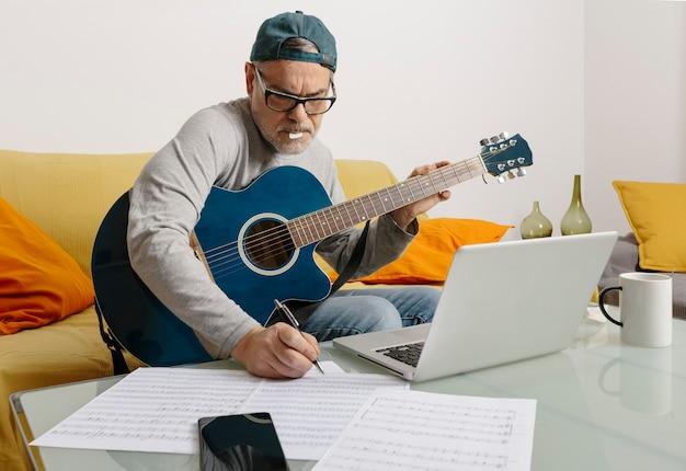 Músico tocando la guitarra y componiendo música por videoconferencia a través de su computadora portátil
