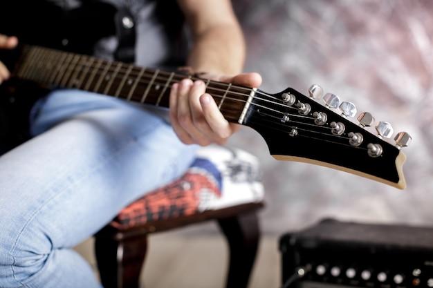 Músico tocando la guitarra eléctrica sobre fondo oscuro. de cerca