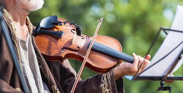 Músico con violín al aire libre durante concierto, panorama
