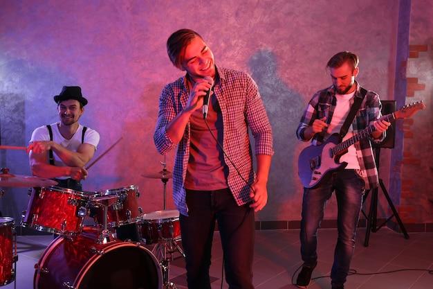 Músicos que tocan instrumentos musicales y cantan canciones en un estudio.