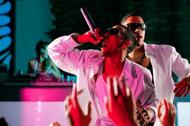 Músicos de rap o hip-hop actuando en el escenario