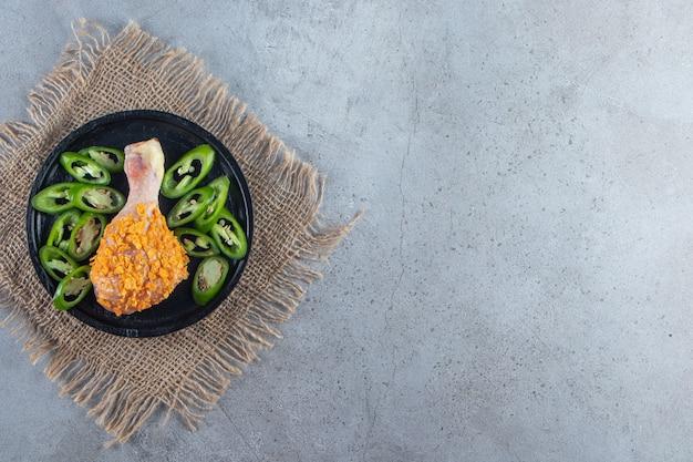 Muslo marinado y pimiento en rodajas en un plato sobre la servilleta de arpillera, sobre el fondo de mármol.