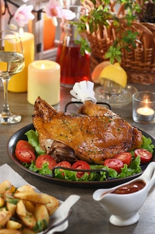 Muslo de pavo al horno en una bandeja de verduras en una mesa festiva en honor al día de acción de gracias.