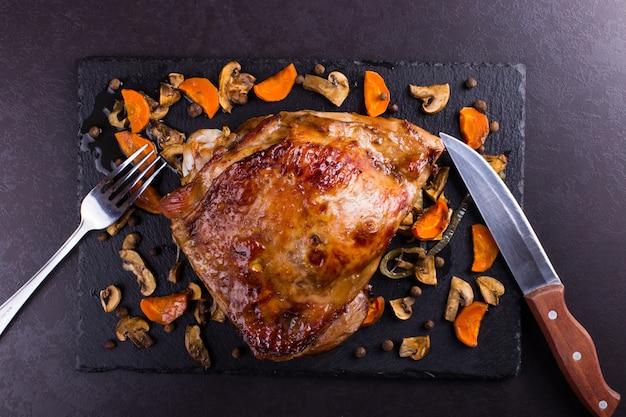 El muslo pavo coció en el horno con las especias en fondo de piedra negro. comida sana. cena de acción de gracias.
