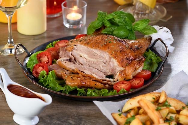 Muslo de pavo horneado en rodajas sobre una bandeja de verduras en la mesa de la cena de acción de gracias
