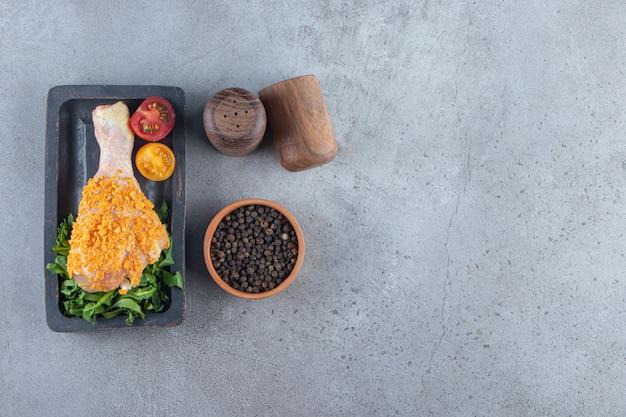 Muslo de pollo adobado en una tabla junto al cuenco de especias, sobre el fondo de mármol.