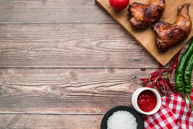 Muslo de pollo asado a la plancha con chiles; sal; salsa y servilleta sobre escritorio.