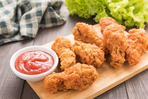 Muslo de pollo frito y verduras en la mesa de madera