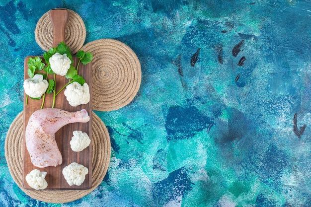 Muslo de pollo marinado y coliflor sobre una tabla para cortar sobre un salvamanteles