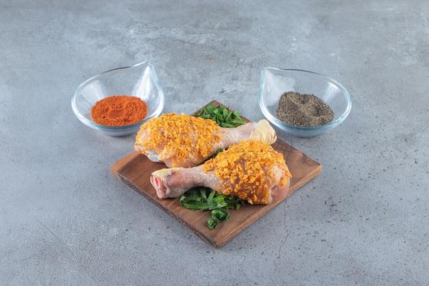 Muslo de pollo marinado en una zona verde sobre una tabla, sobre la superficie de mármol.