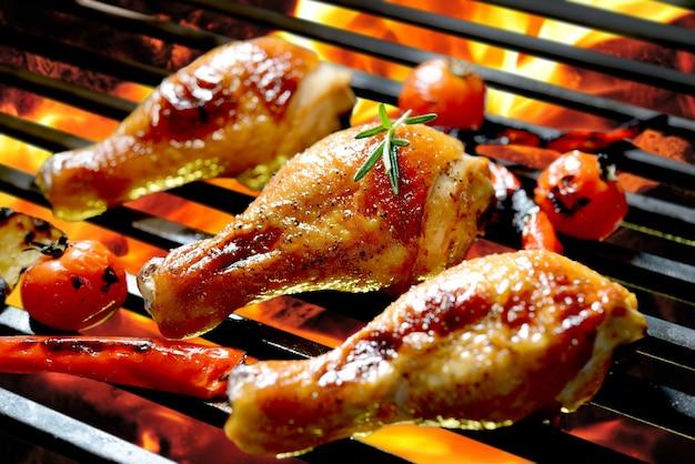 Muslo de pollo a la parrilla sobre la parrilla en llamas