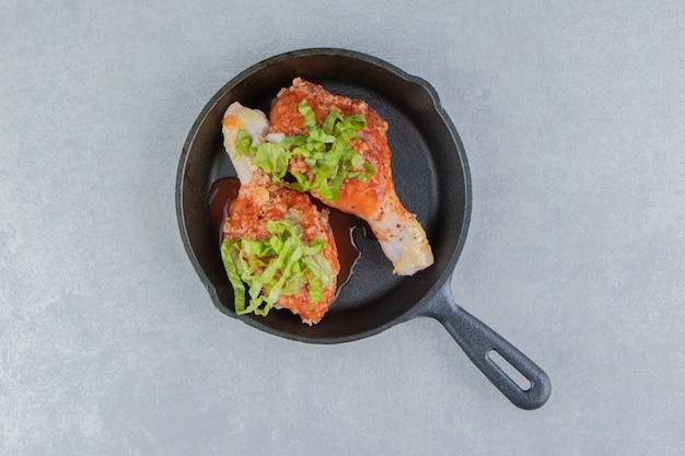 Muslo de pollo y verde en la caldera, sobre la superficie blanca