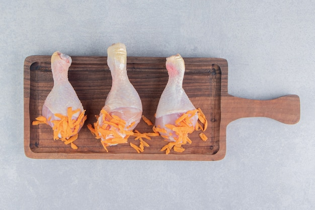 Muslo de pollo y zanahoria rallada en el tablero, sobre la superficie de mármol